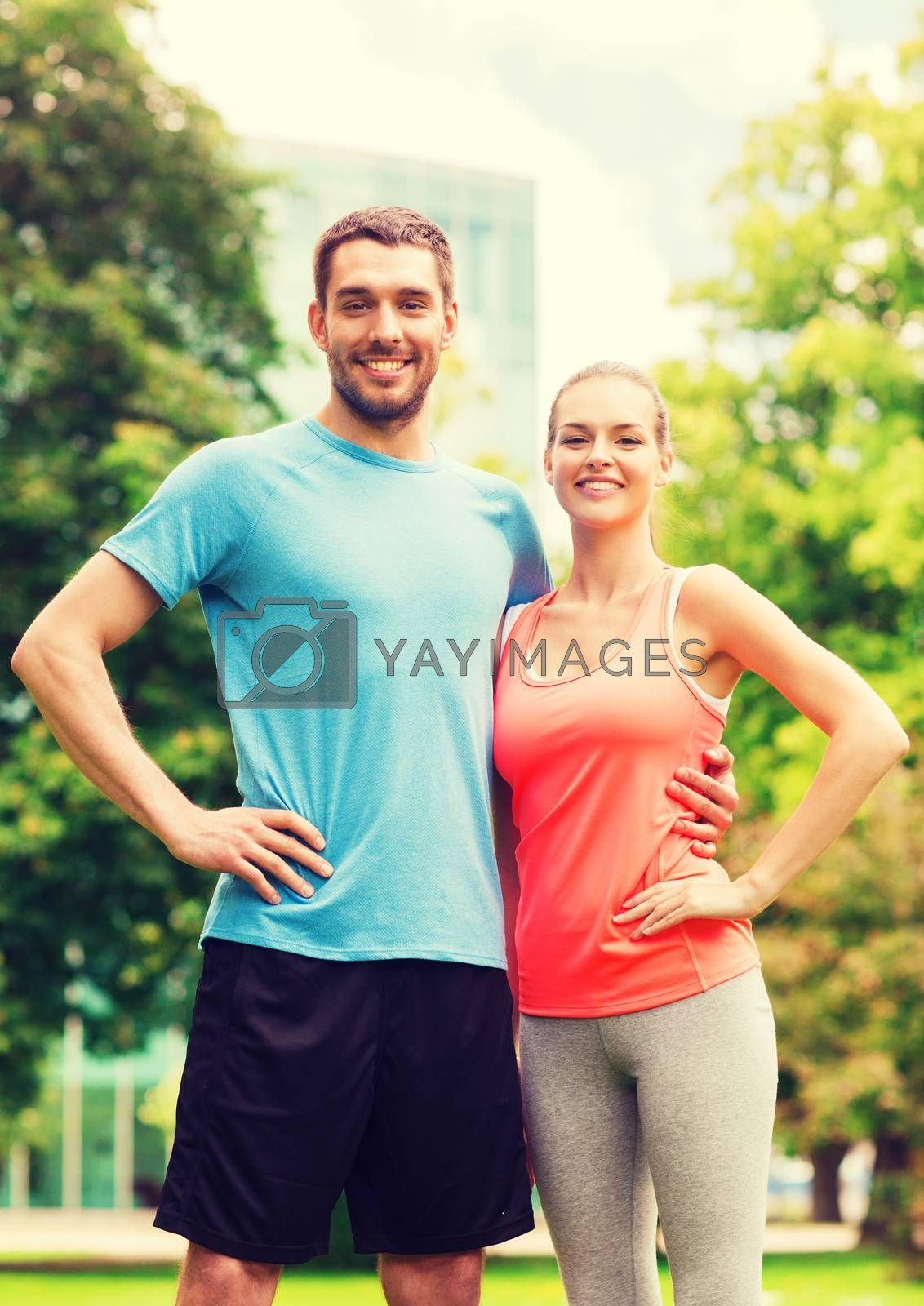 fitness, sport, friendship and lifestyle concept - smiling couple outdoors