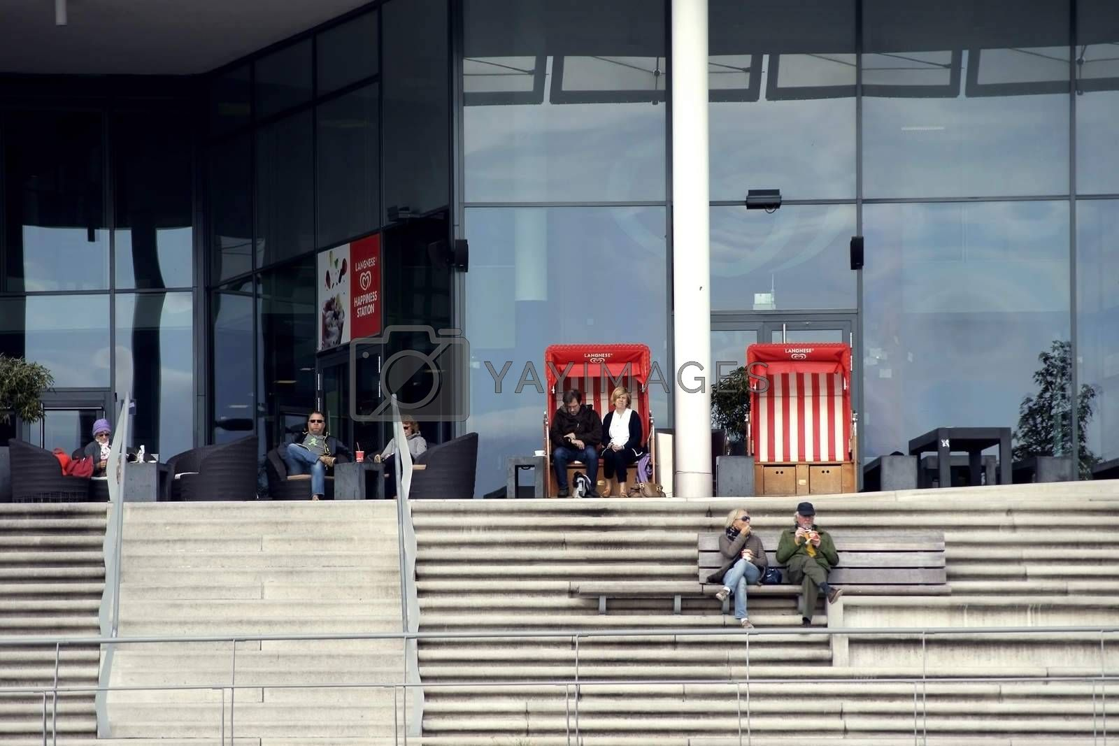 Hamburg, Germany - September 22, 2014: Visitors of restaurants and ice cream parlors in the Harbor city Hamburg sit in beach chairs and at tables on a terrace in good weather on September 22, 2014 in Hamburg.