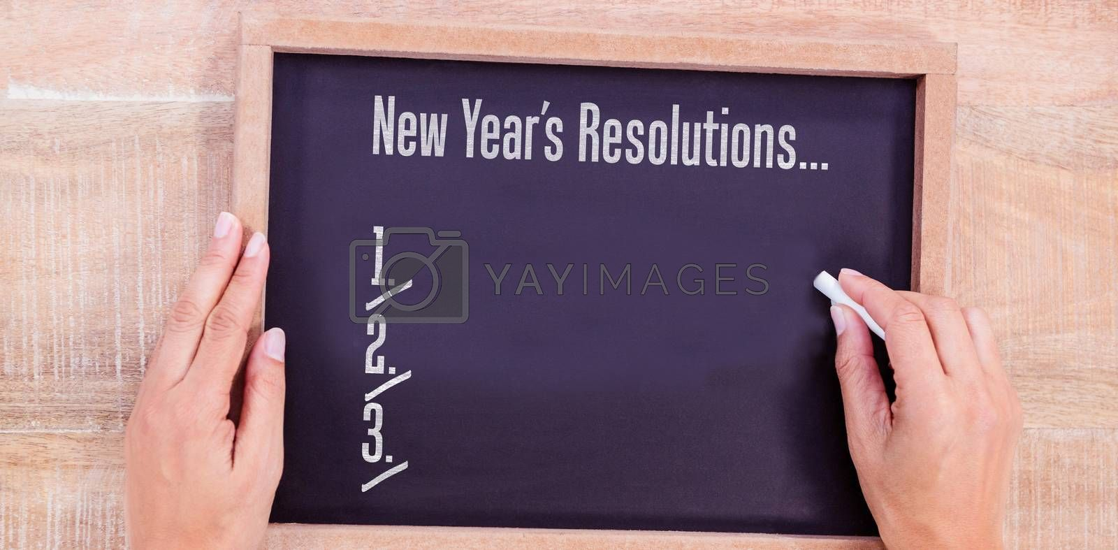 New years resolution list against hand writing on chalkboard