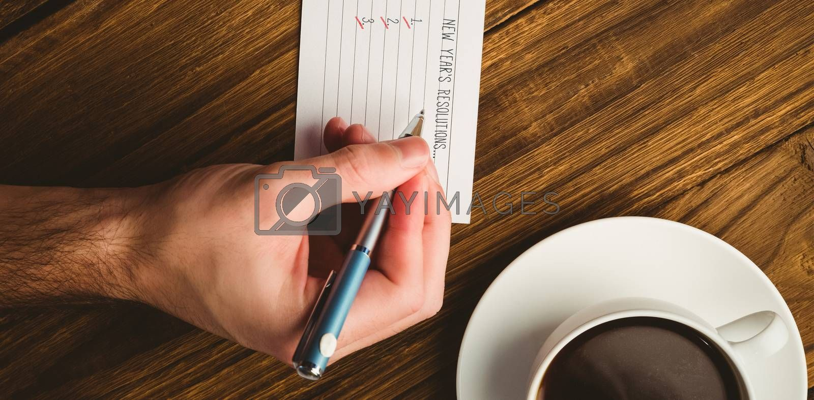 New years resolution list against cropped hand writing on paper at desk with coffee cup