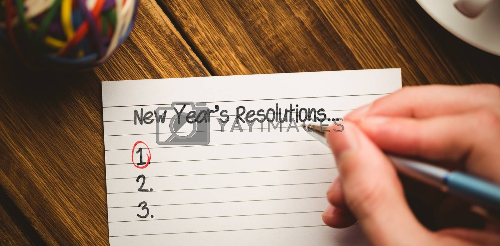 New years resolution list against cropped hand writing in book with cup on table