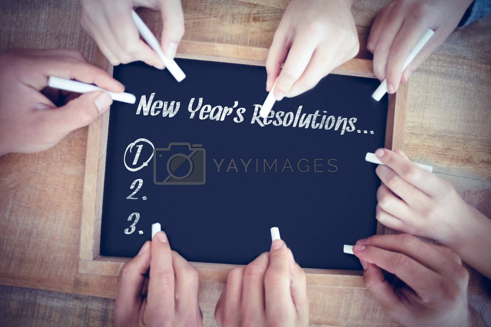 New years resolution list against hands writing on chalkboard