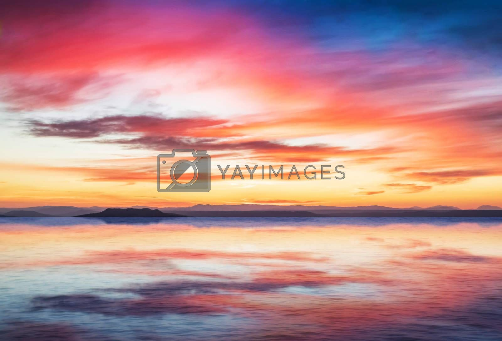 sunset scene on quiet sea with mountains in background, colorful sky with soft clouds