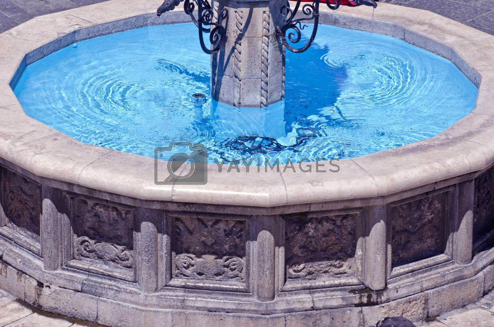 Royalty free image of Old decorative city Fountain with blue water by alis_photo