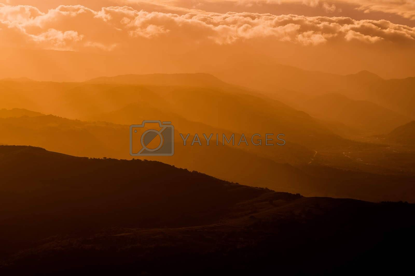 mountains silhouette at sunset with fog, natural light tint blue