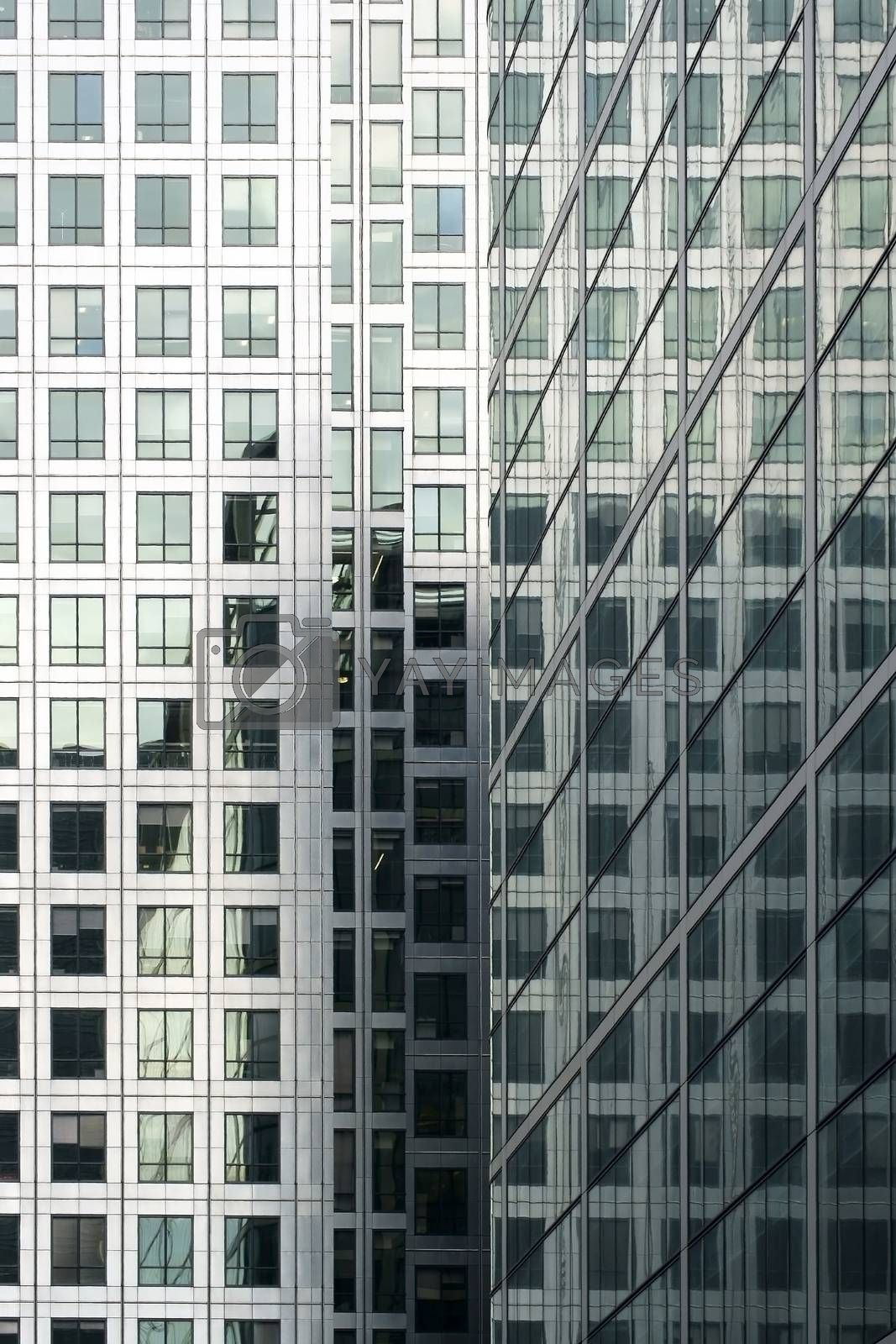 The corner of a modern high-rise building in which the respective parts of the buildings reflect in each other.