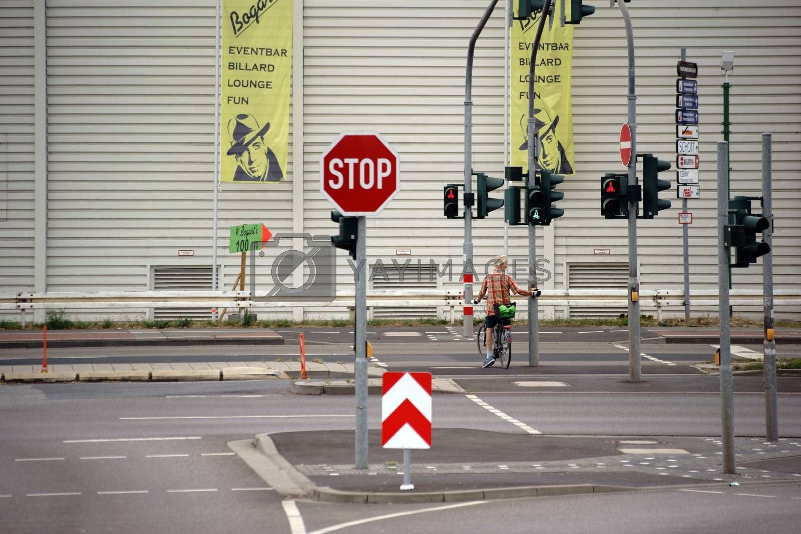 Mainz, Germany - August 14, 2015: A cyclist stands at a red light intersection in front of a hardware store on a street with many traffic signs on August 14, 2015 in Mainz.