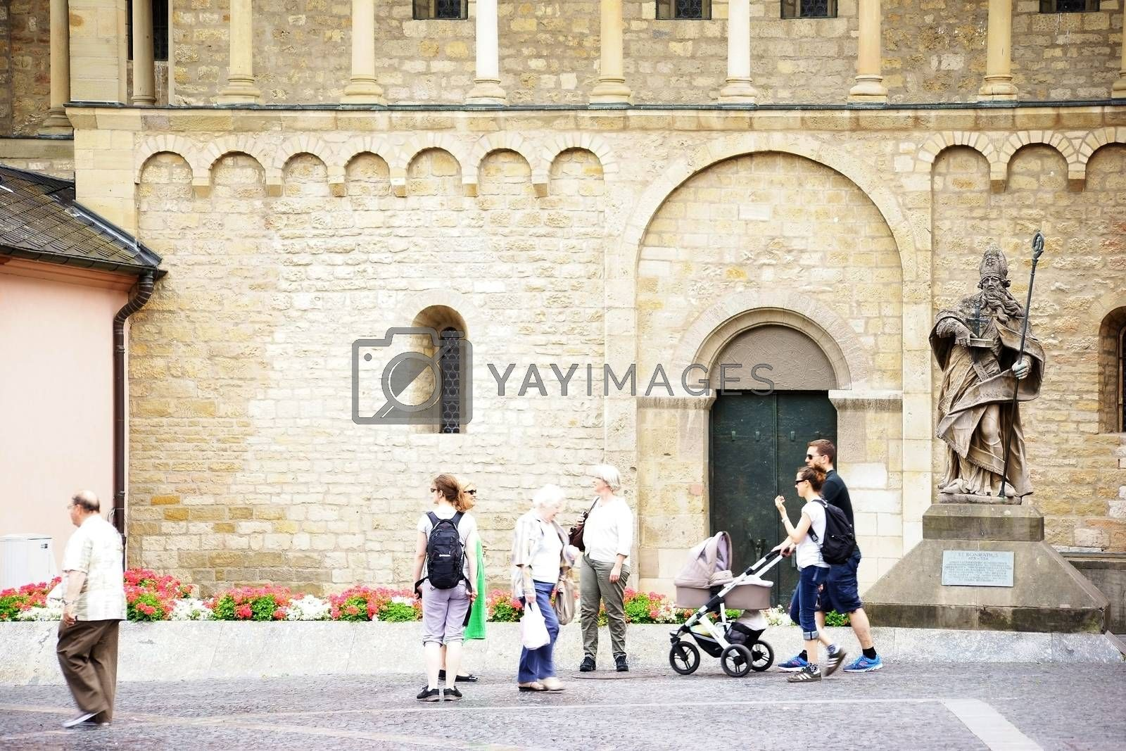 Mainz, Germany - June 25, 2015: Families and tourists passing the sculpture of St. Boniface in front of the Mainz Cathedral with flowerbeds on June 25, 2015 in Mainz.