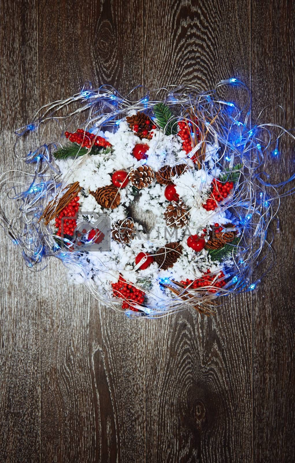 Christmas wreath and light on a hardwood background