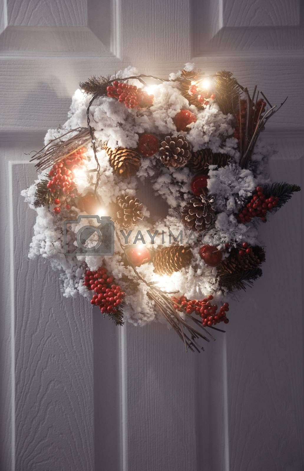 Christmas wreath and light on a white front door