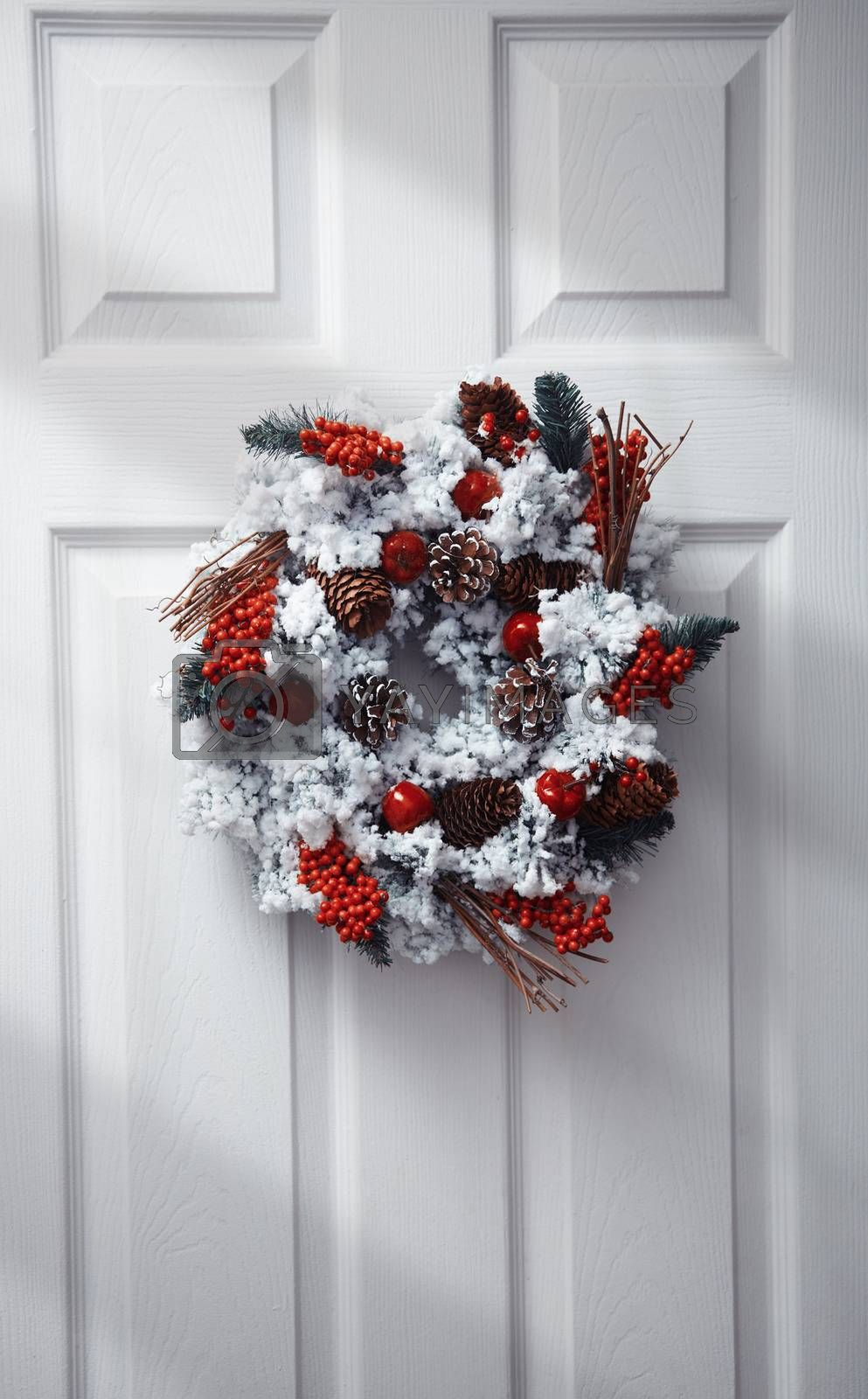 White front door decorated by Christmas wreath. Vertical photo
