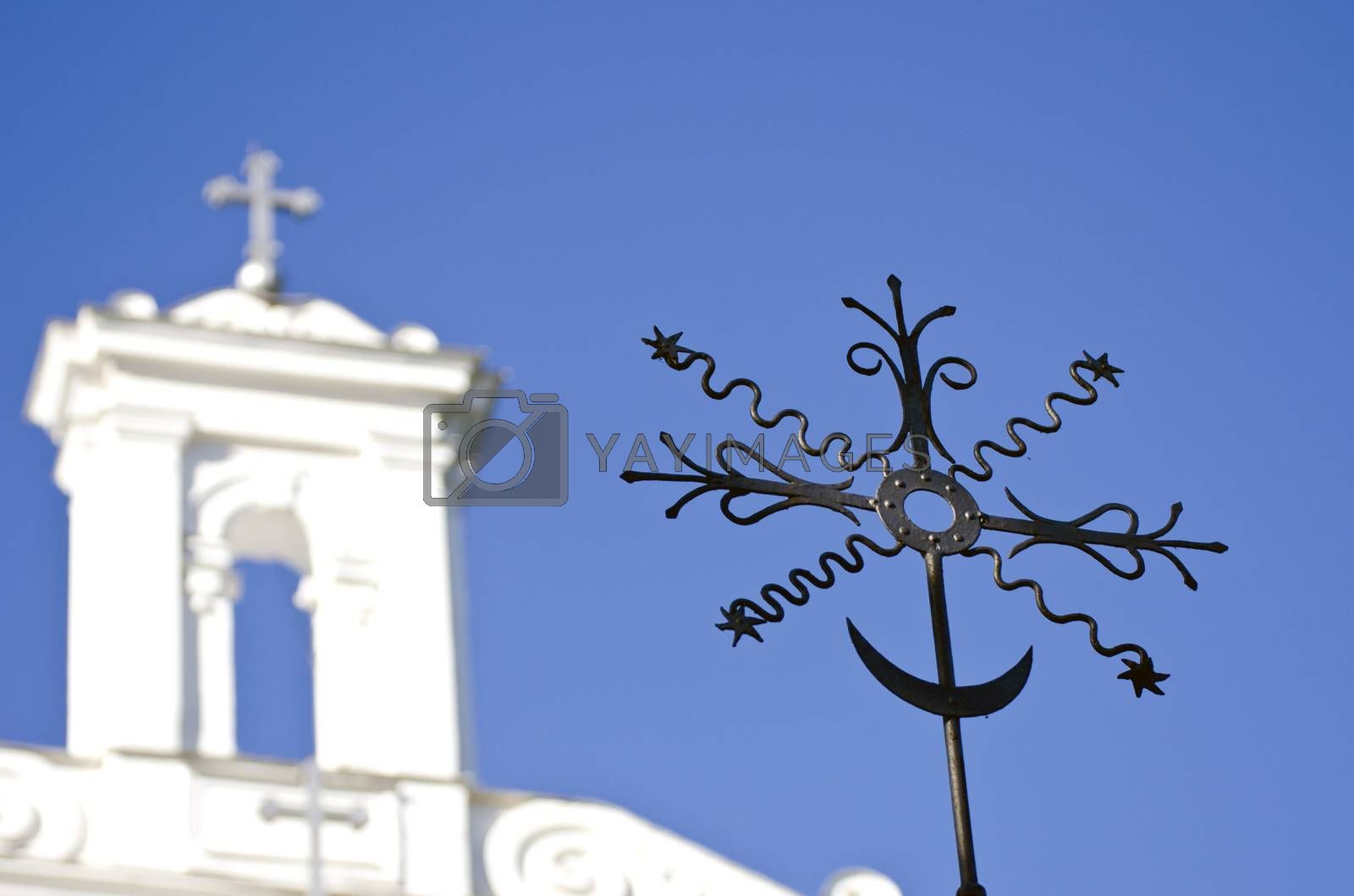 Royalty free image of Closeup of black metal cross with a white church in the background by alis_photo