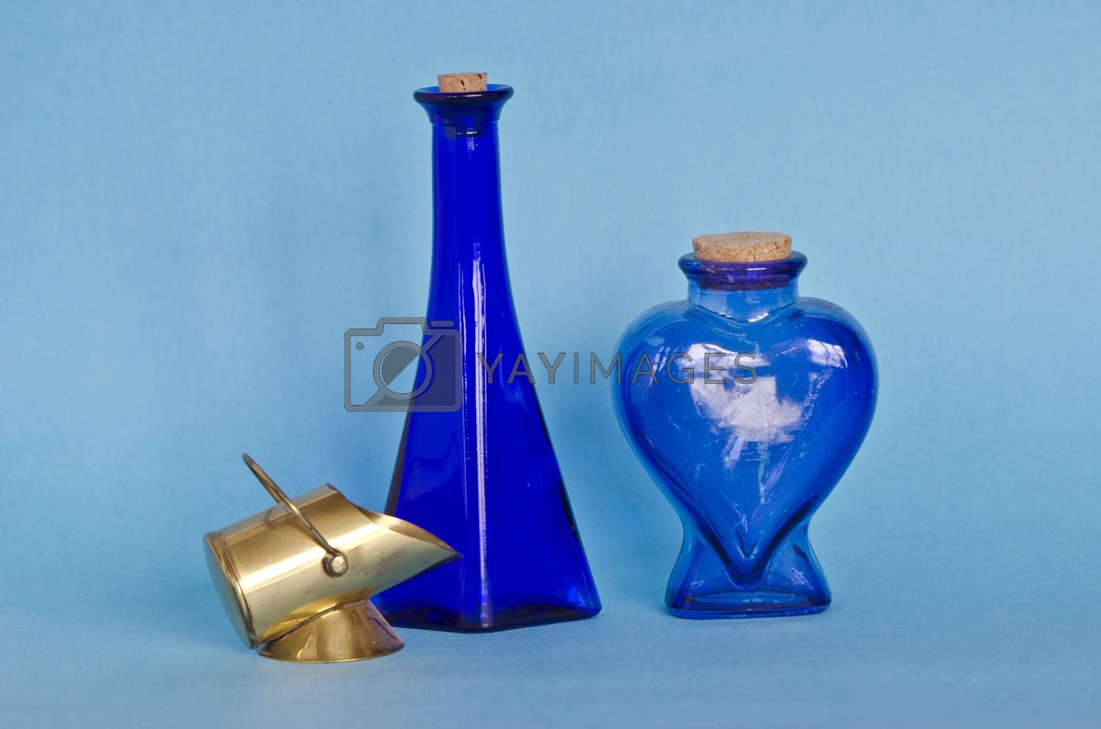 Royalty free image of Two blue glass bottles with decorative brass object by alis_photo