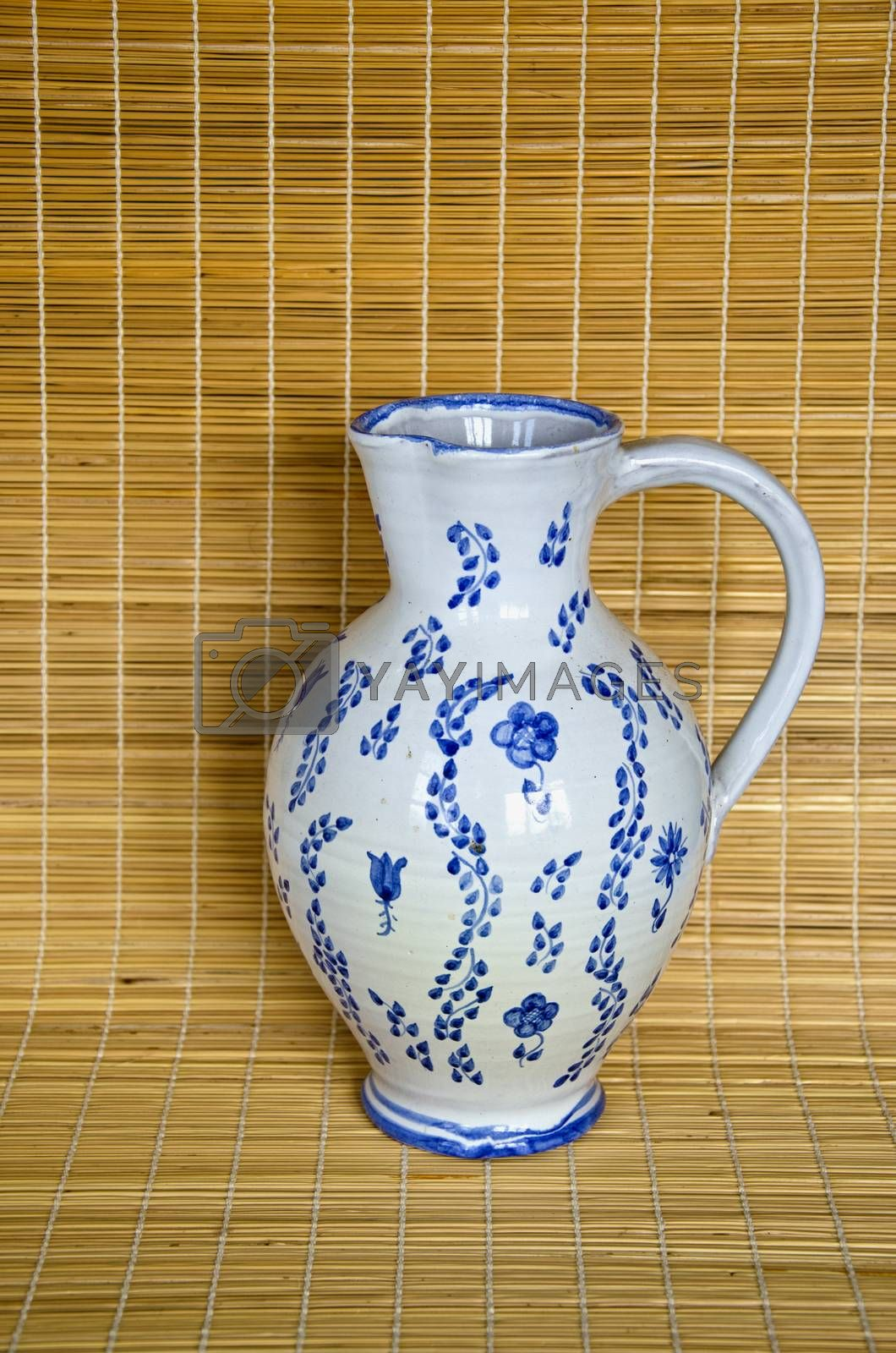 Royalty free image of Clay jug on bamboo material background by alis_photo