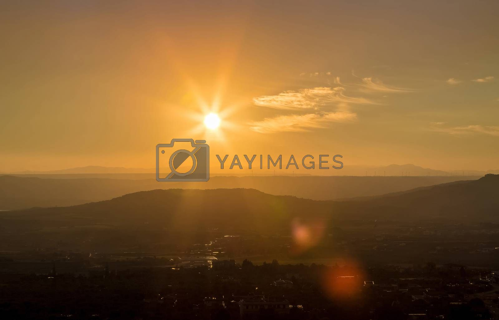 sunset scene with mountains in background, colorful sky with soft clouds and city in foreground, industrial view with sun light and lens flare