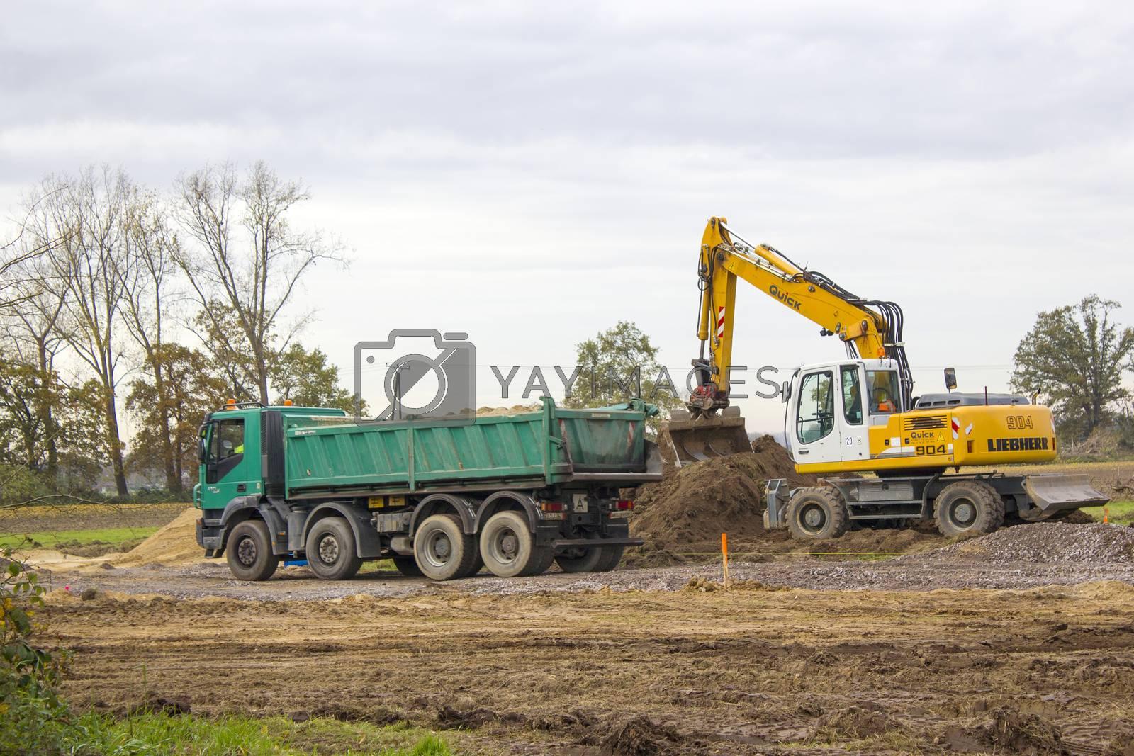 Excavator loading dumper truck tipper in sand pit
