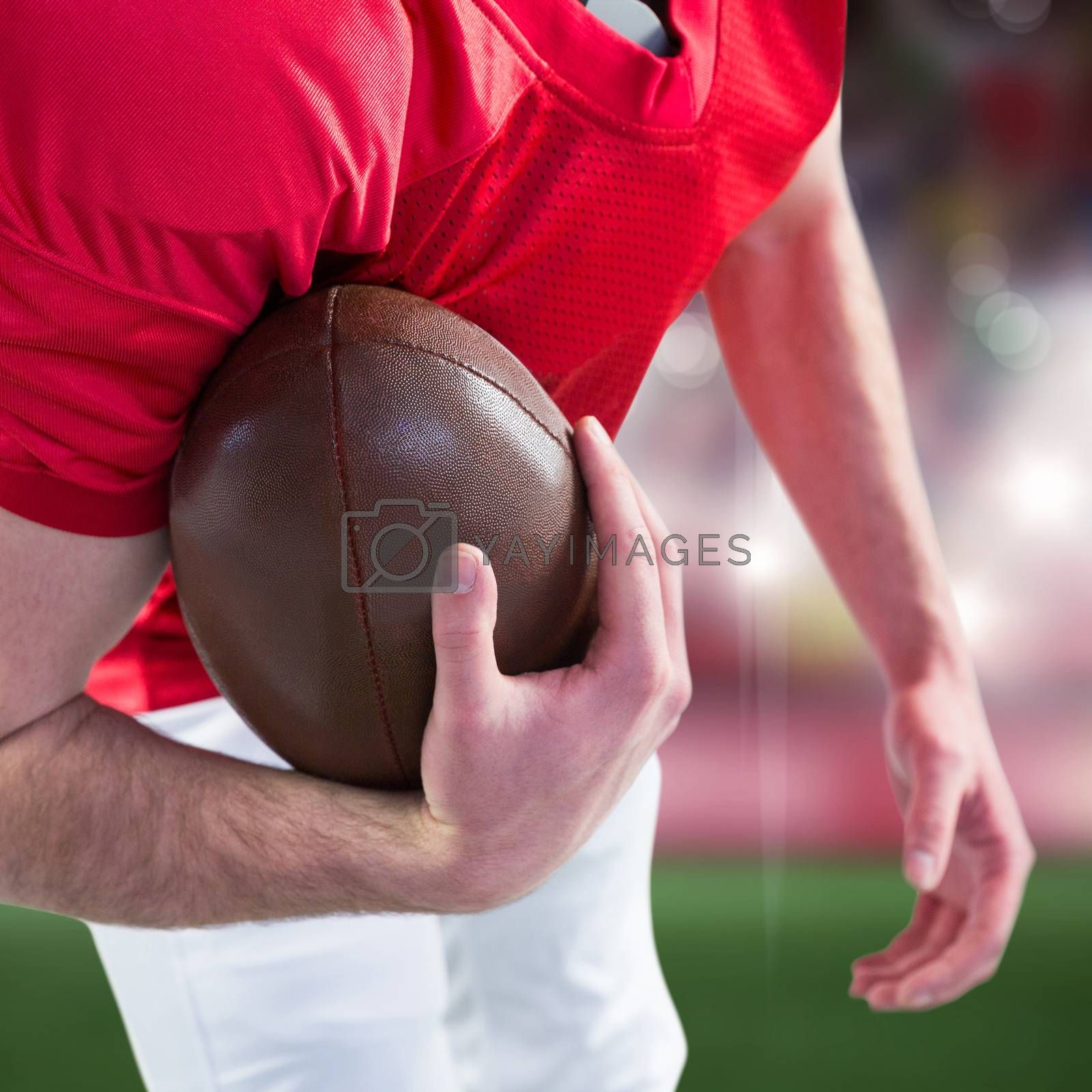 Royalty free image of Composite image of american football player taking a ball on her hand  by Wavebreakmedia