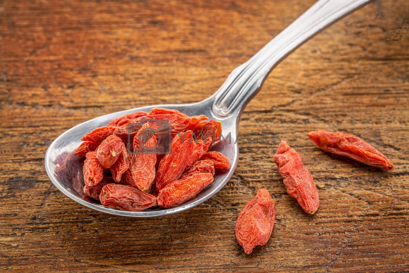 tablespoon of dried goji berries against rustic, scratched wood surface