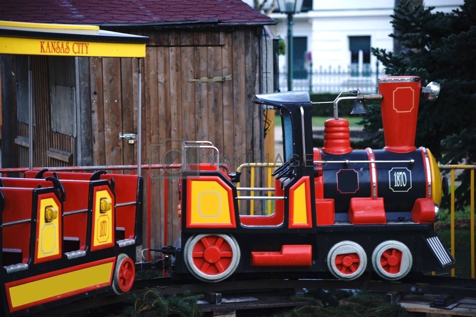 A children's carousel on a Christmas market with rails and a locomotive.