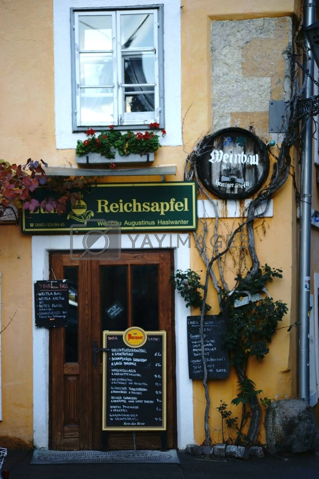 Baden, Austria - November 14, 2015: The restaurant to the Imperial Orb decorated with signs and dining tables and overgrown with climbing plants on November 14, 2015 in Baden near Vienna.