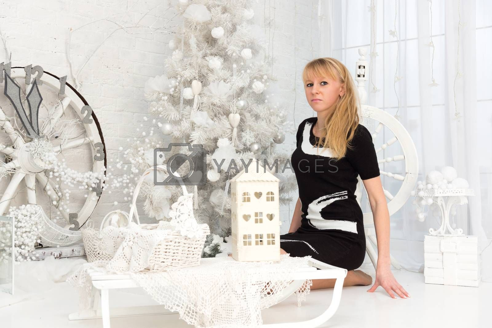 The photo shows a girl sitting in front of Christmas tree
