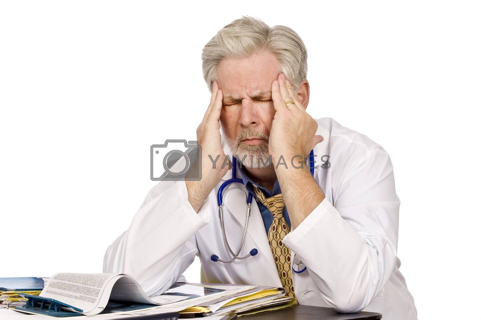 Horizontal shot of a tired doctor at his desk with a bad headache.