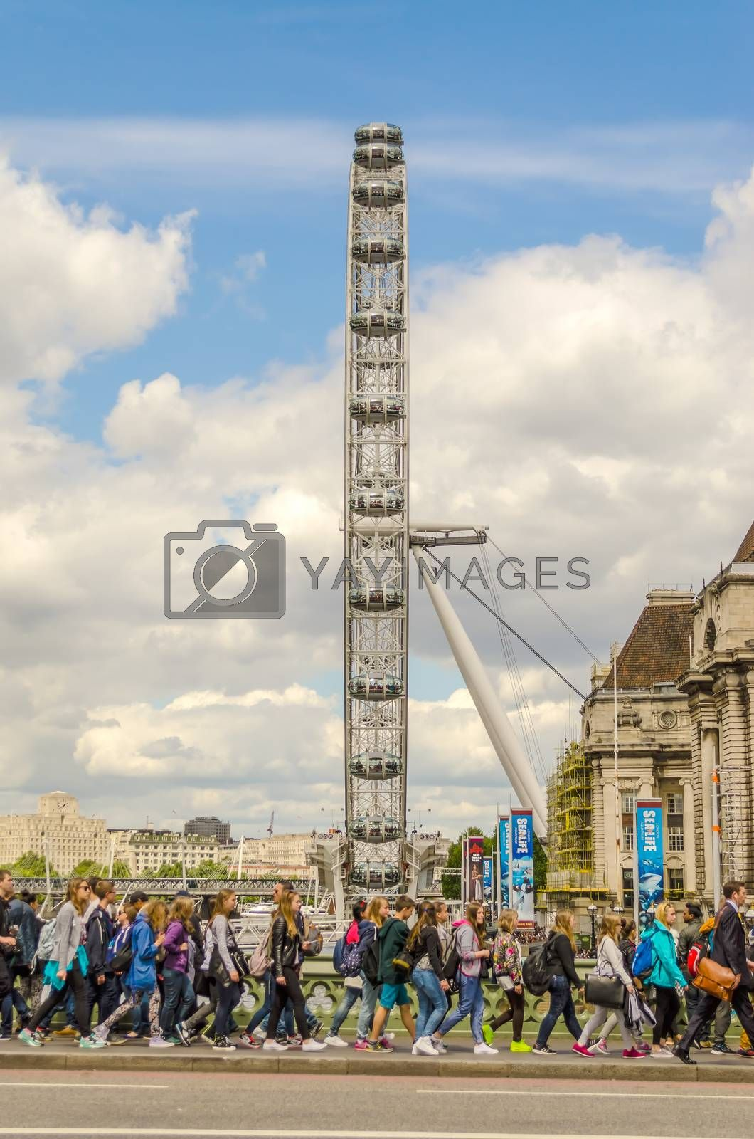 LONDON - MAY 28: Tourists on Westminster Bridge with London Eye on background, May 28, 2015. The ferris wheel is 135 metres (443 ft) tall and the wheel has a diameter of 120 metres (394 ft)