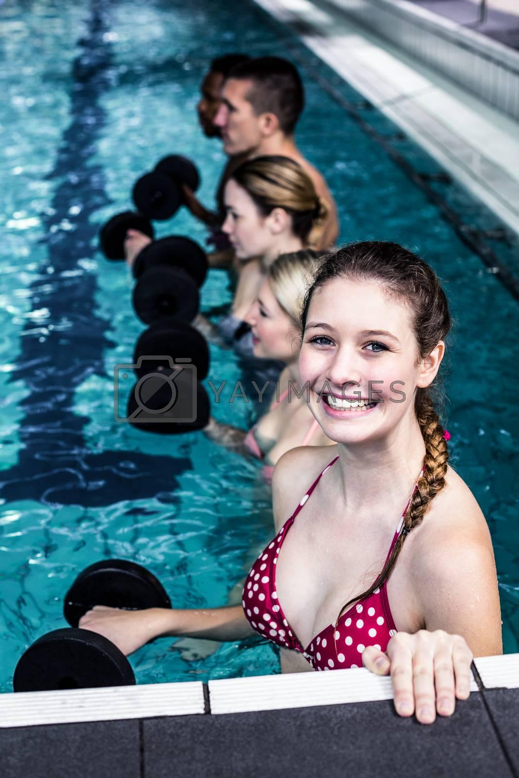 Fit people doing an aqua aerobics class in swimming pool