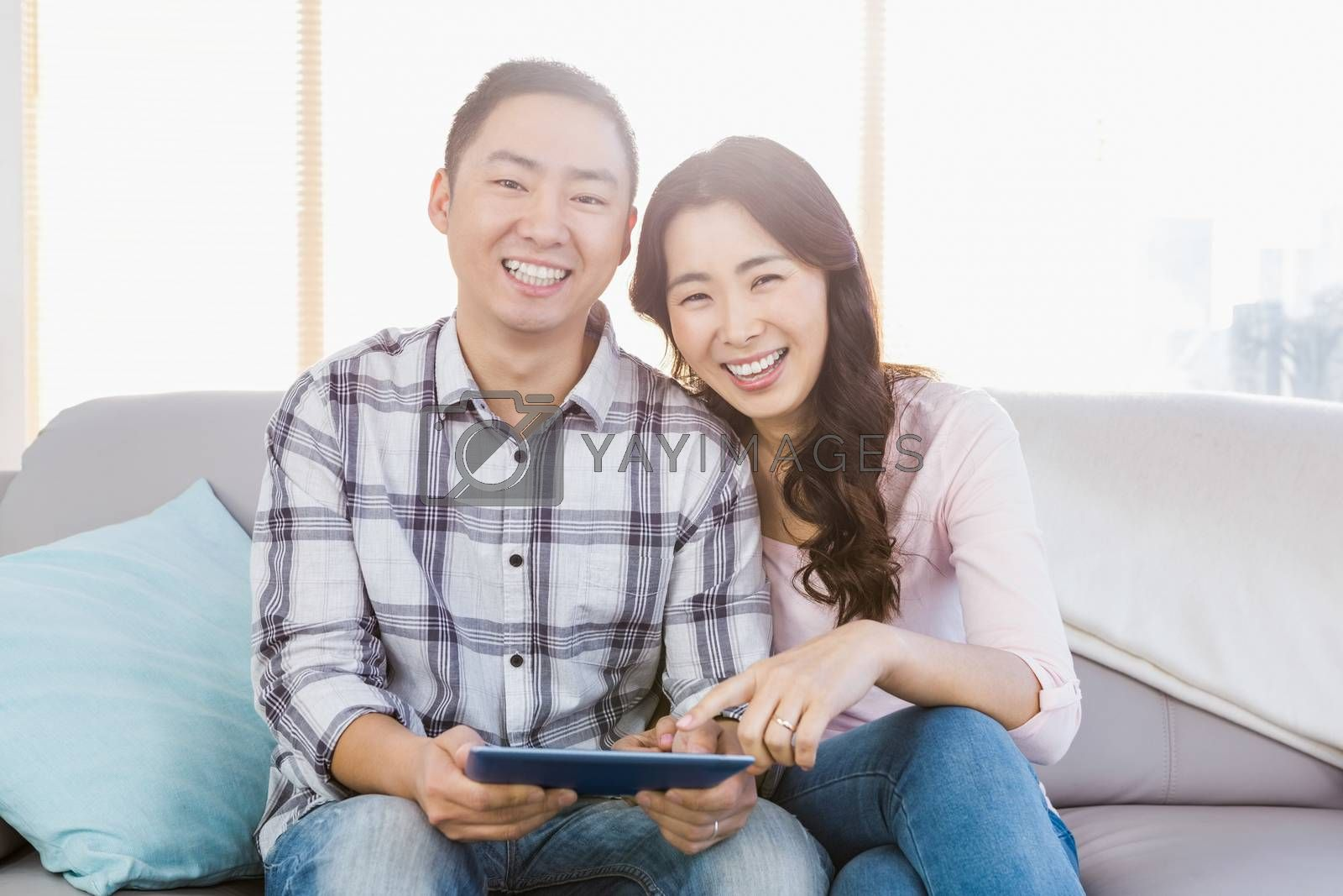 Young happy couple holding digital tablet while sitting at home