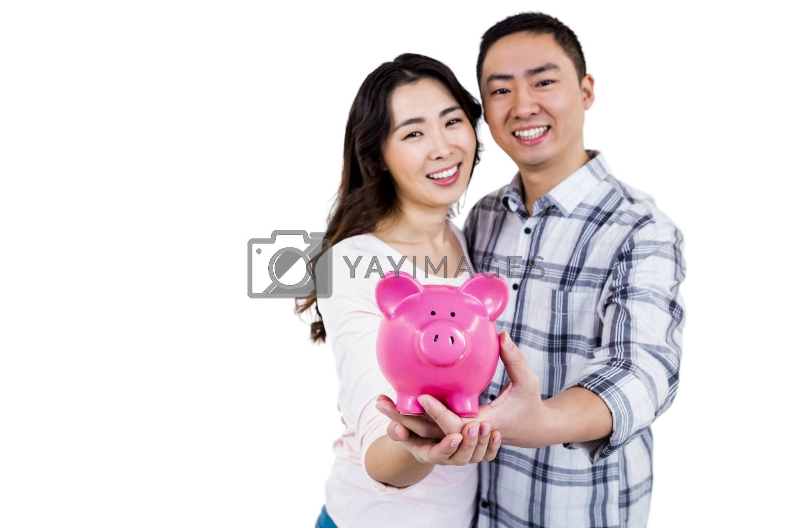 Portrait of cheerful couple holding piggy bank while standing against white background