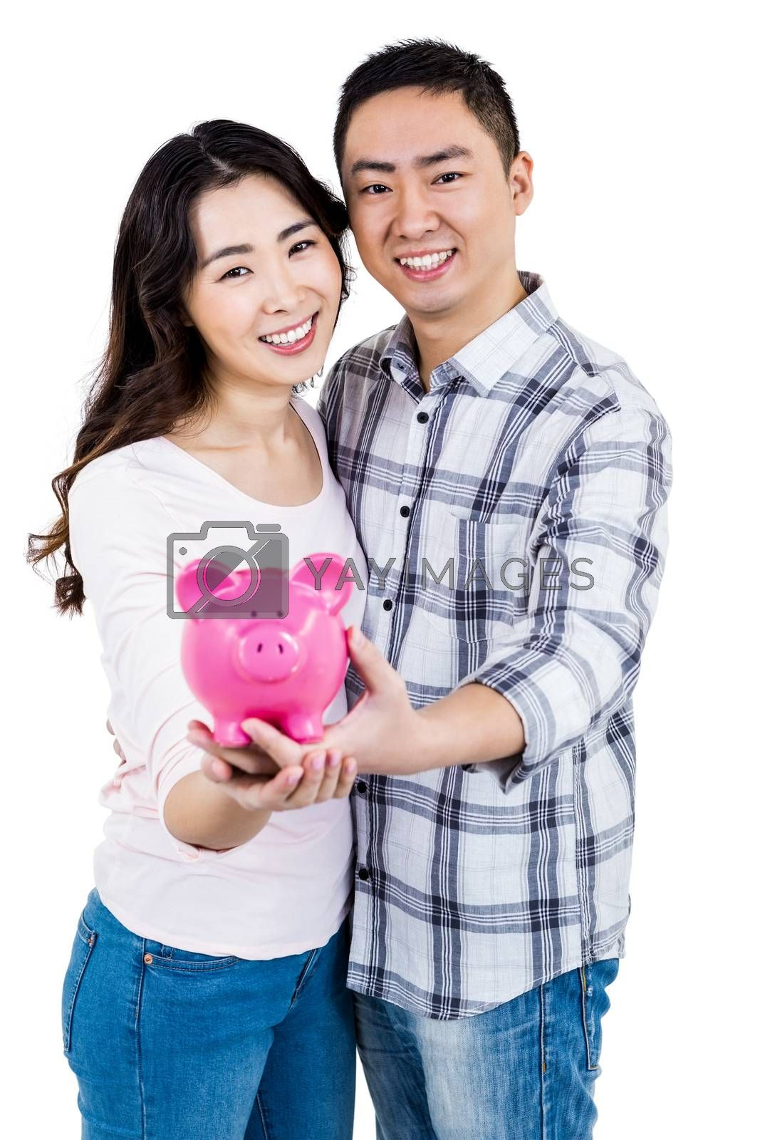 Portrait of happy smiling couple holding piggy bank against white background