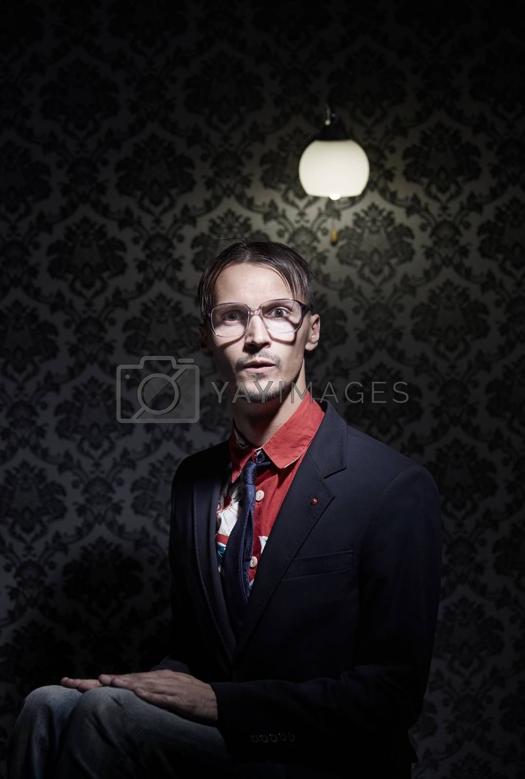 Young hipster man sitting in the dark room. Vertical photo