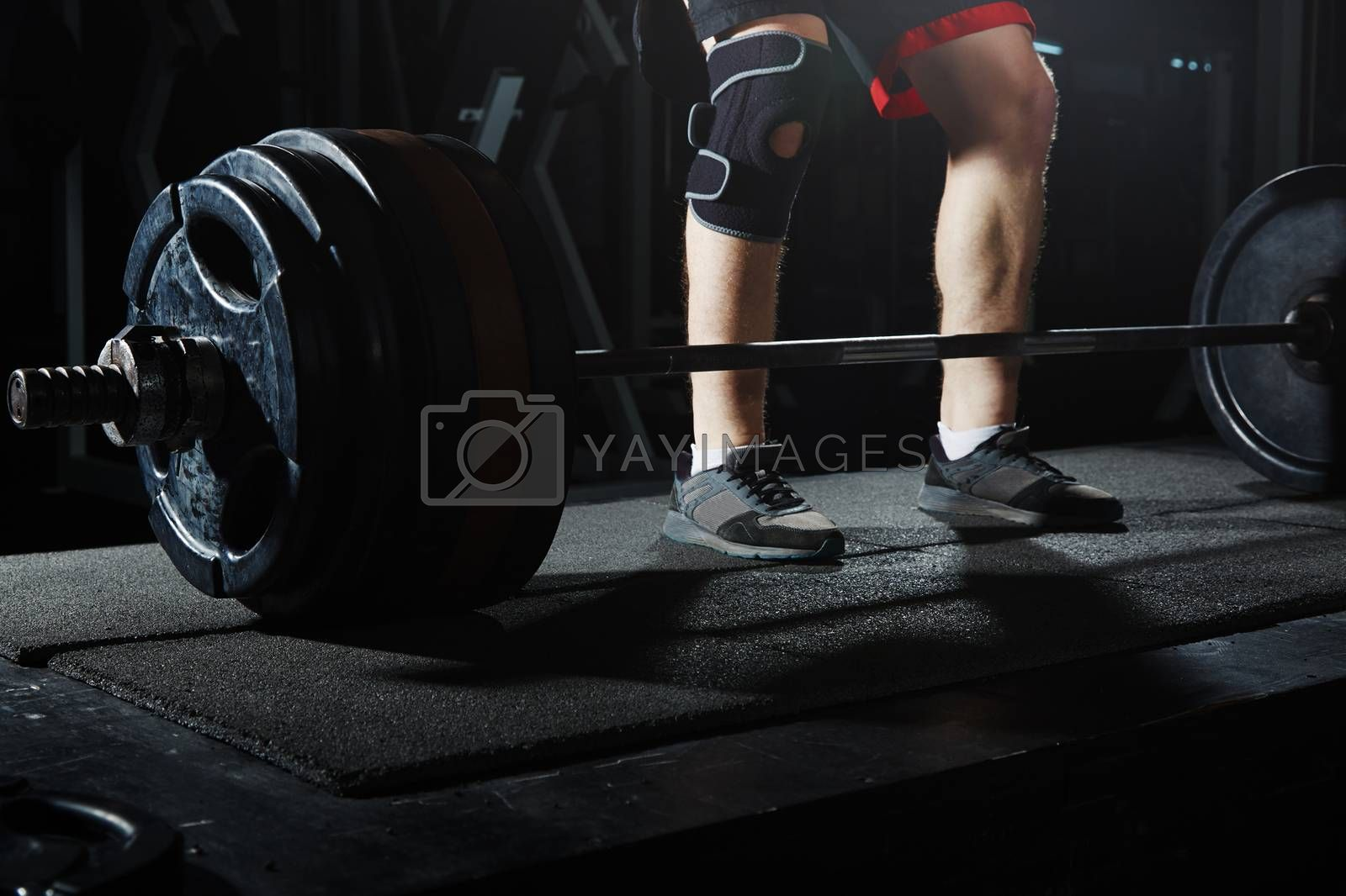Man at the heavy barbell in fitness club. Close-up view