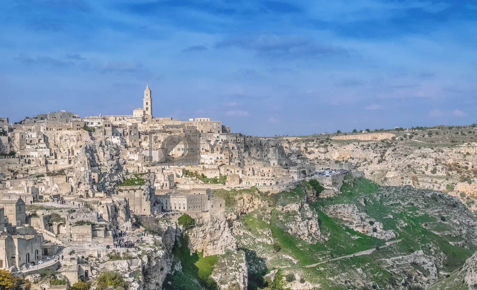 panoramic view of typical stones (Sassi di Matera) and church near gravina of Matera UNESCO European Capital of Culture 2019 under blue sky. Basilicata, Italy