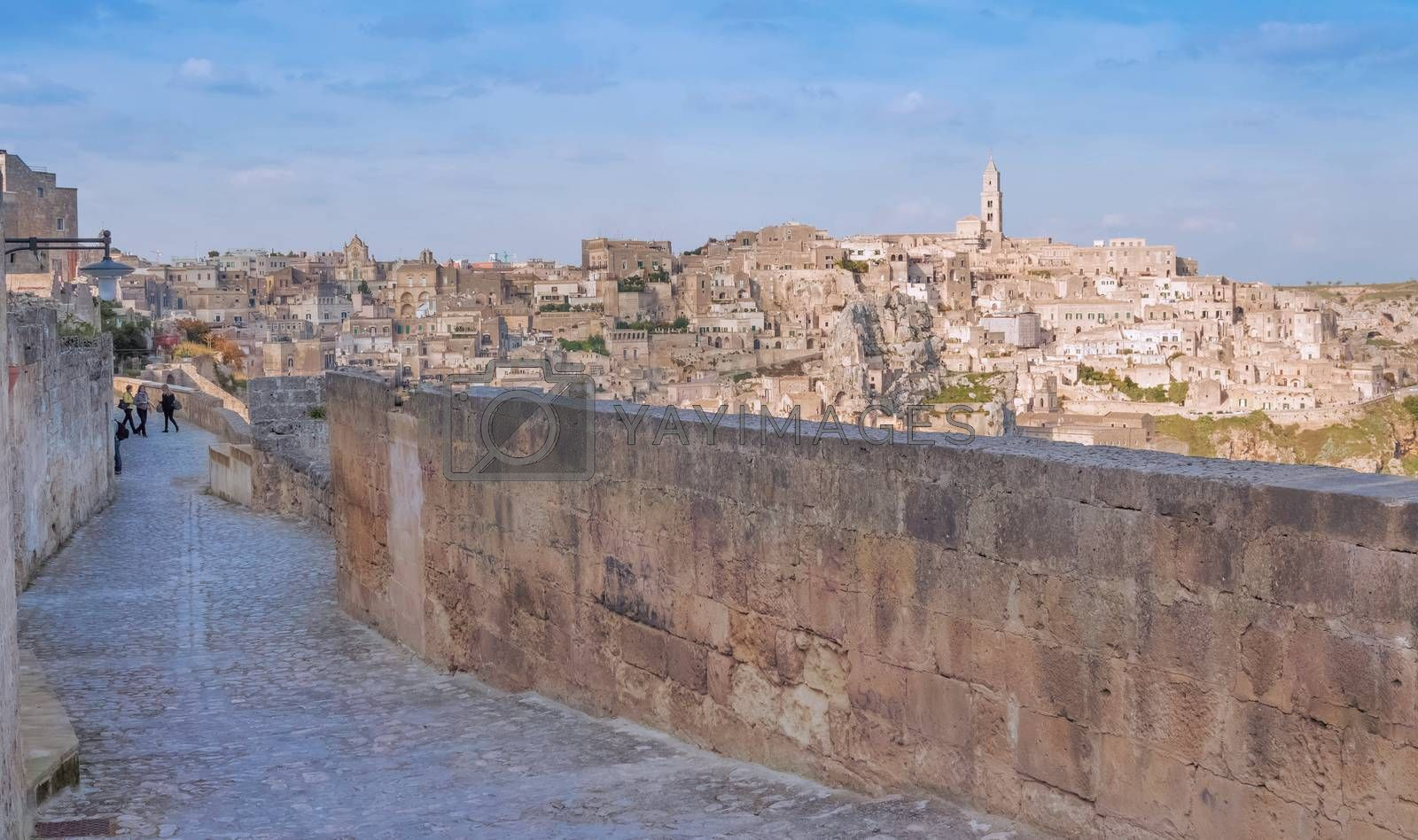 panoramic view of typical stones and church of Matera shot from typical old street, under blu sky. Basilicata, Italy