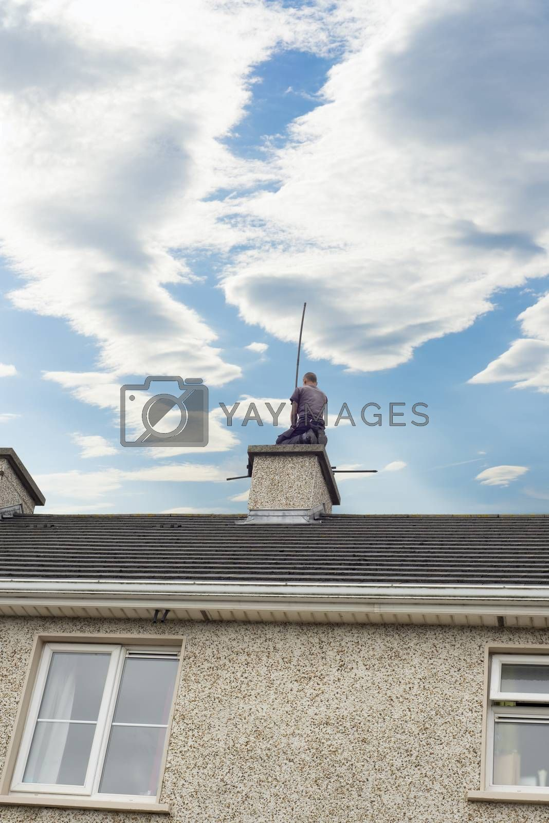 chimney sweep busy cleaning chimney on top of a house