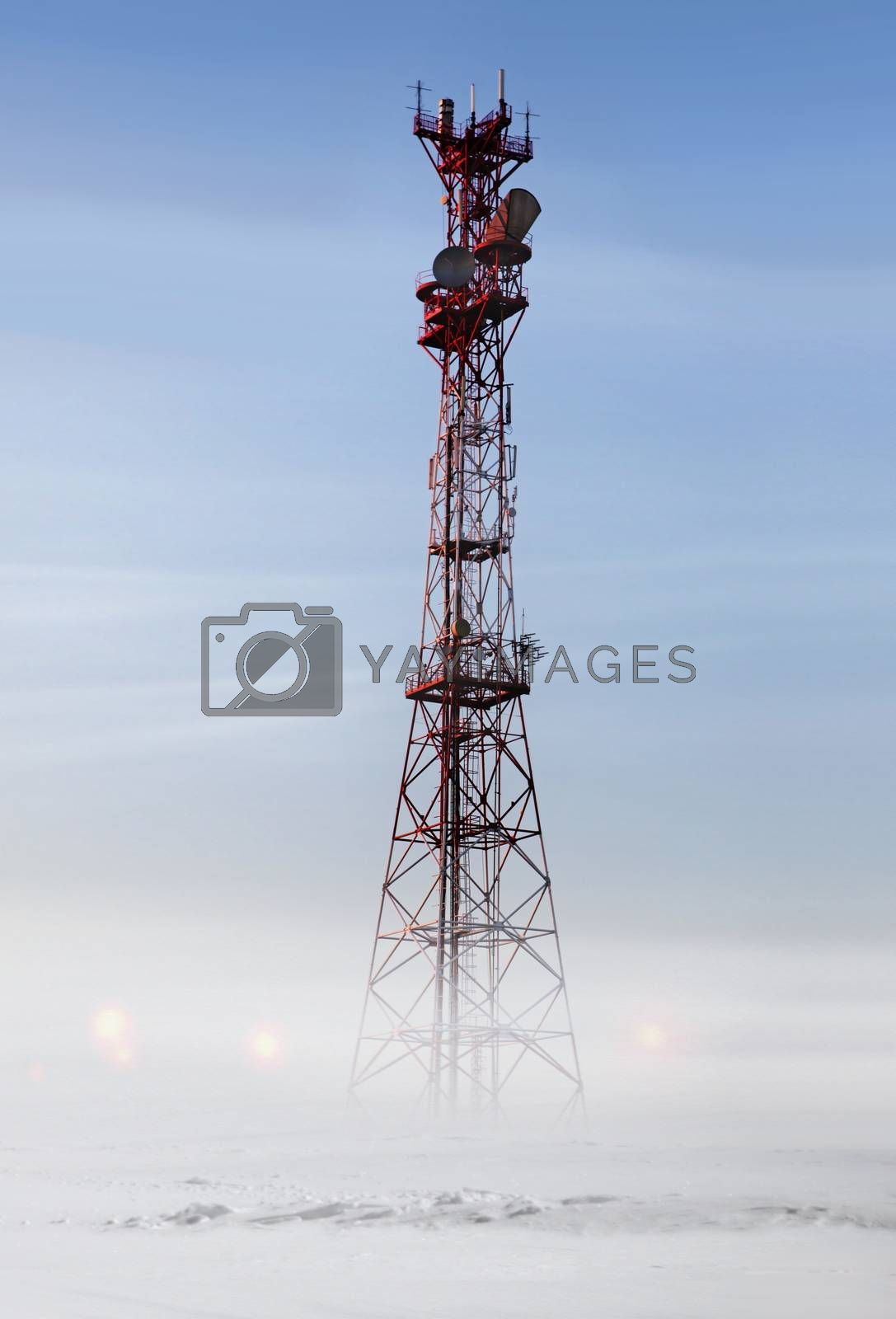 Red communication tower in snowstorm at winter