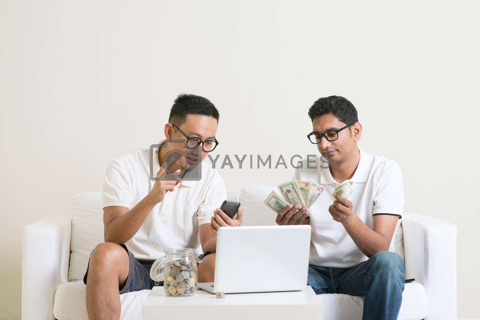 Asian men working from home. Young guys counting cash with partner, earning money from their successful online business.