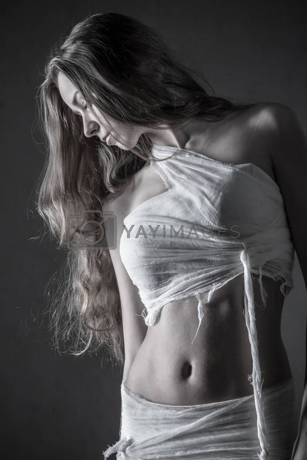 Pretty young woman with a bandage dressings on her body over grey background