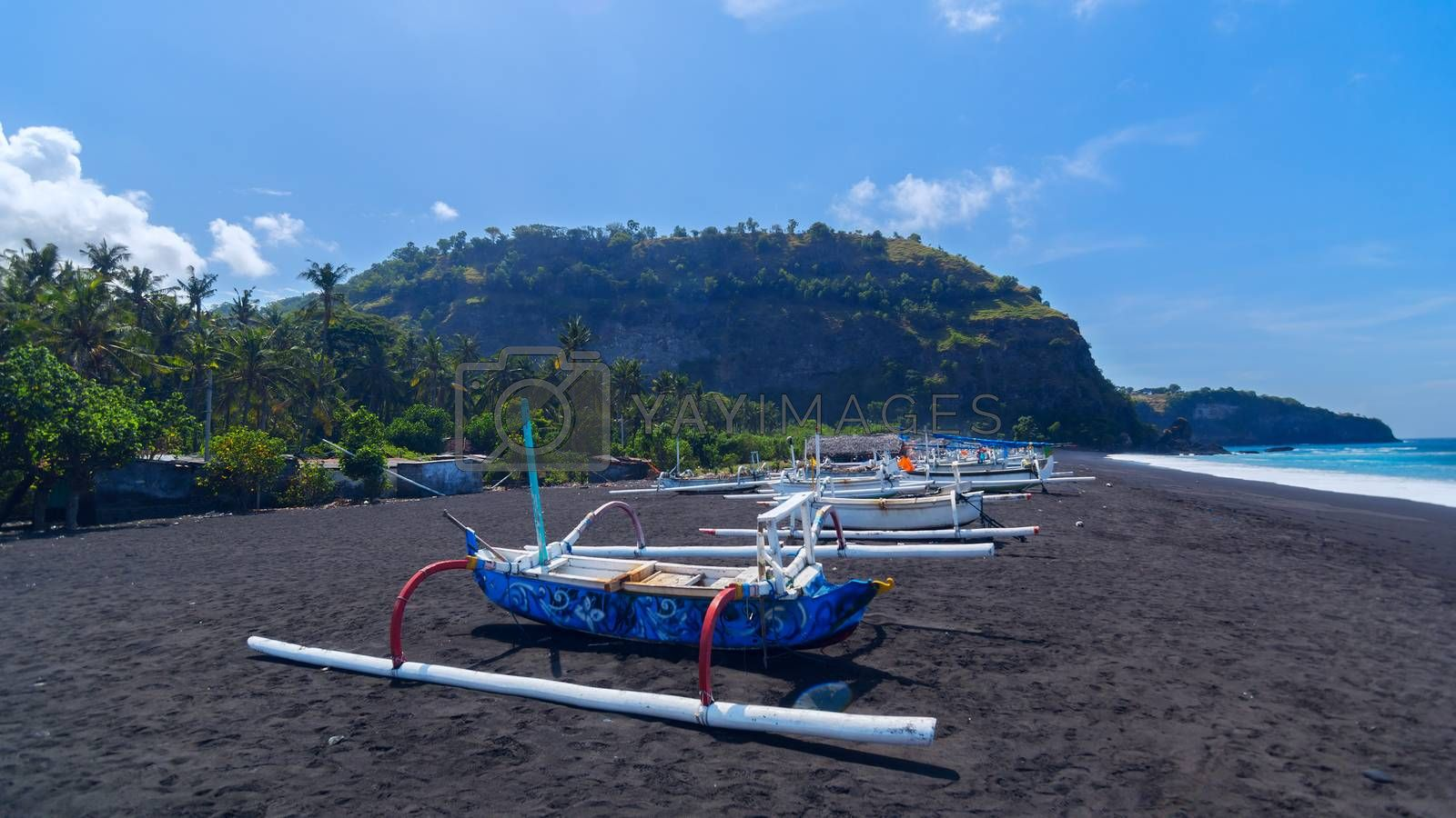 Junk on the beach of black sand on the island of Bali in Indonesia. Summer sunny day.