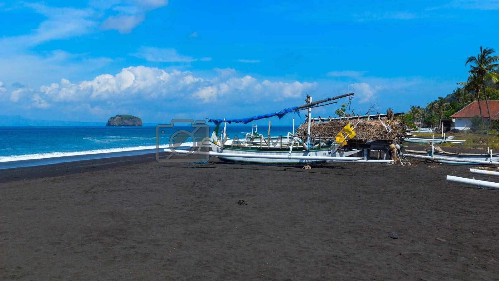 Boats on the beach of black sand on the island of Bali in Indonesia. Summer sunny day.