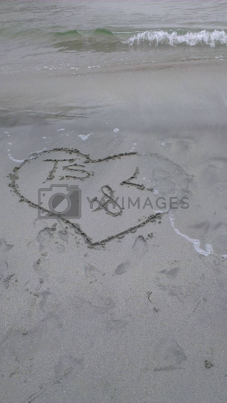 A heart drawn in the sand with initials in it.