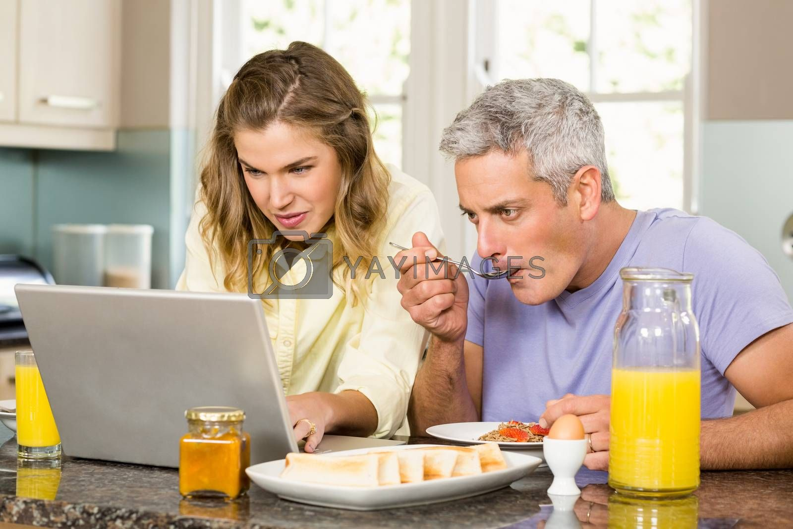 Happy couple using laptop and having breakfast in the kitchen
