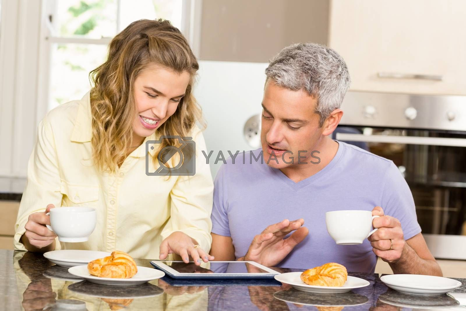 Happy couple using tablet and having breakfast in the kitchen