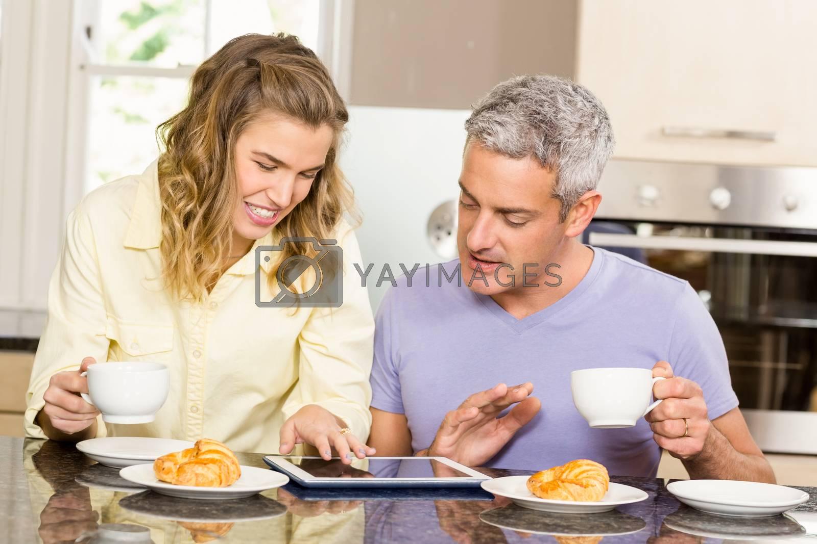 Happy couple using tablet and having breakfast by Wavebreakmedia