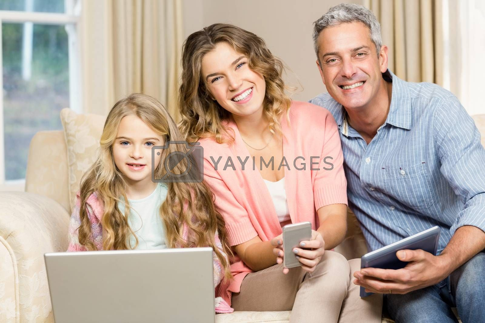 Happy family on the sofa using laptop, tablet and smartphone