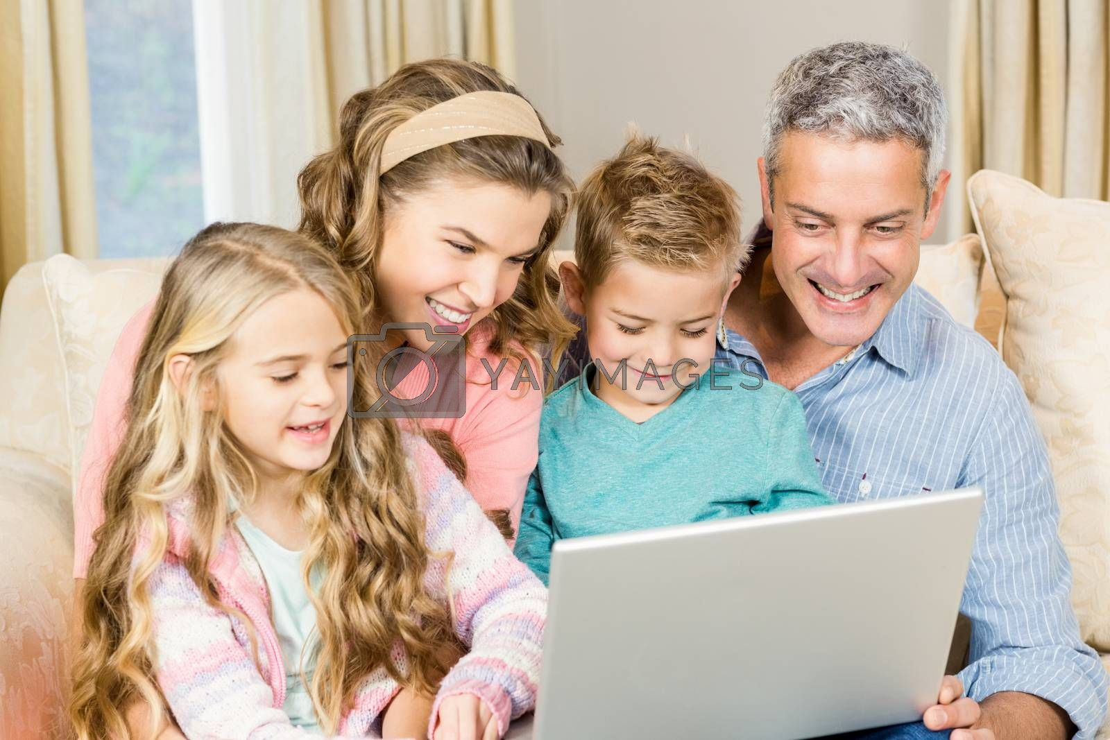 Happy family using laptop on the sofa in living room