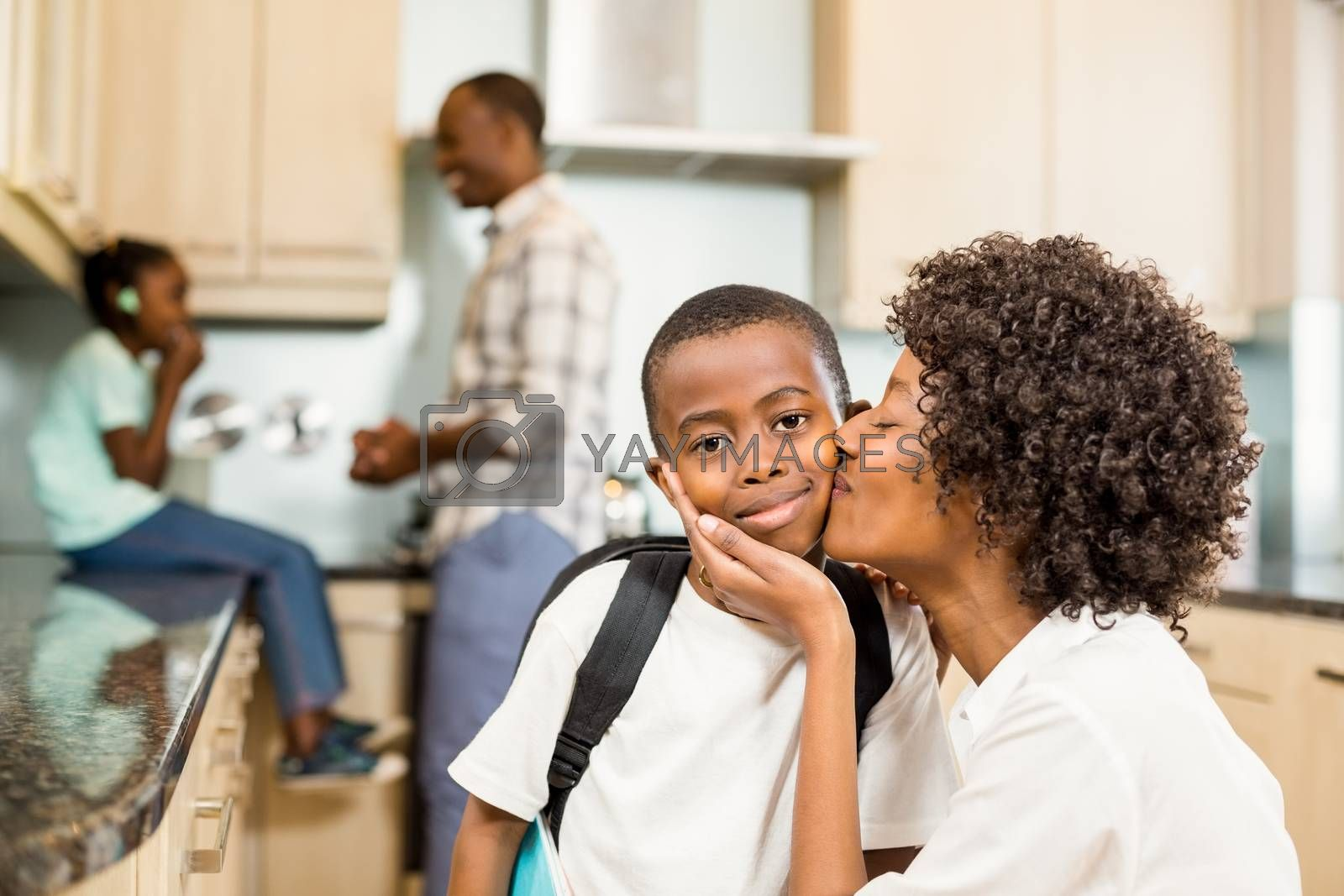 Mother kissing son with backpack in the kitchen