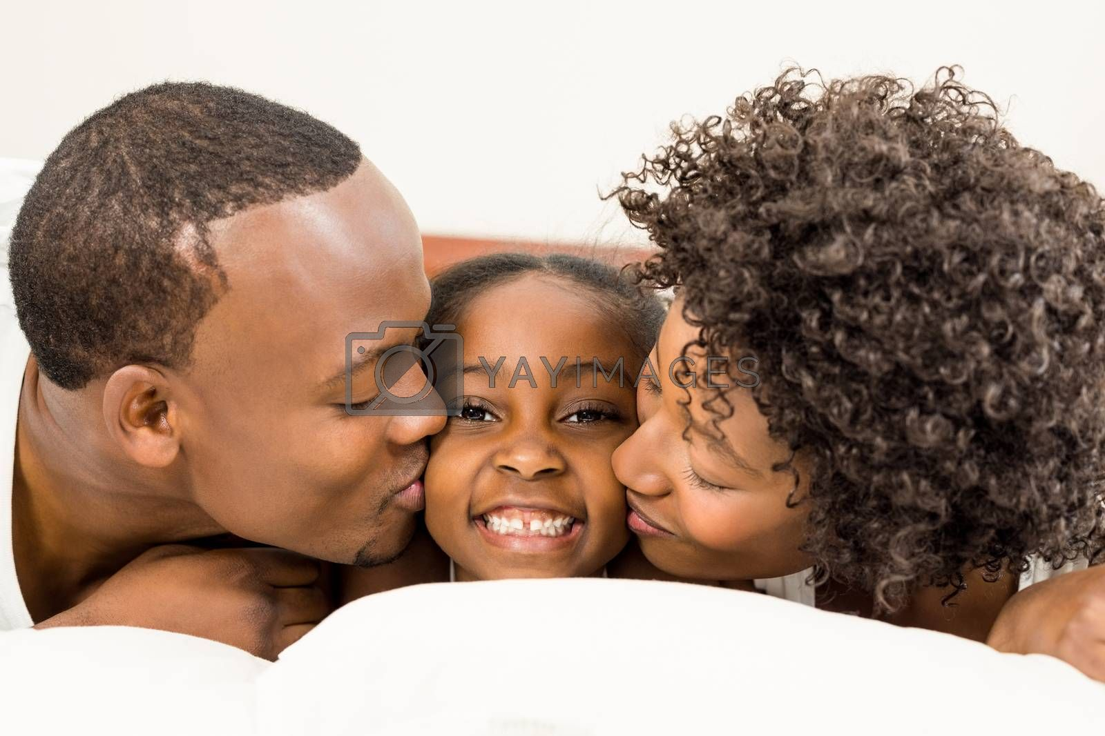 Smiling family lying in bed at home