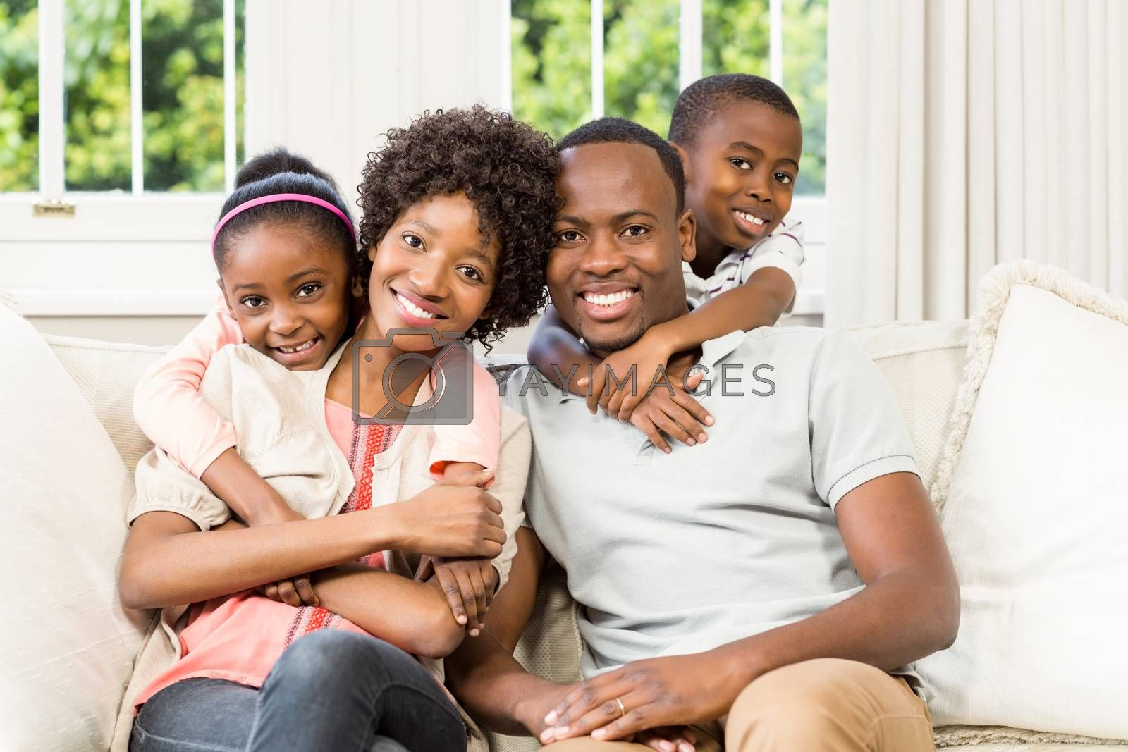 Smiling family sitting on the couch together at home